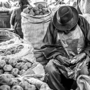 Eingeschlafener Kartoffelschäler auf Markt in Peru. Falling asleep potato peeler at market in Peru.